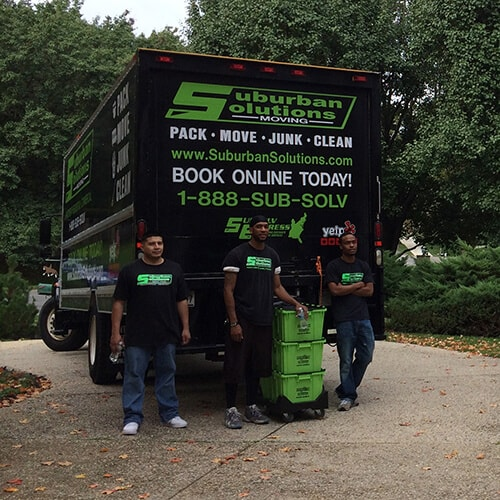 Suburban Solutions' junk removal crew posing in front of the truck
