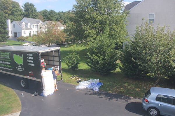 Suburban Solutions' junk removal crew loading mattress in one of the junk trucks