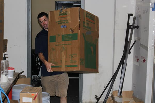 One of our employees taking out a box full of undesired junk