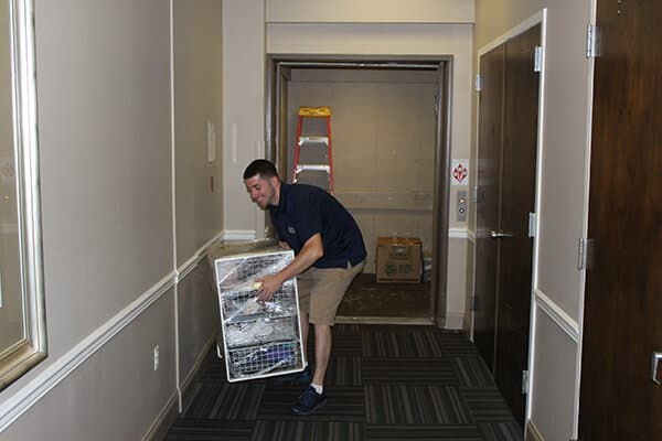 A member of Suburban Solutions' junk removal team taking out some clutter