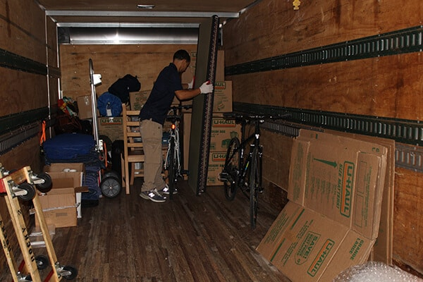 A member of Suburban Solutions' veteran NYC junk removal team loading one of the junk removal trucks