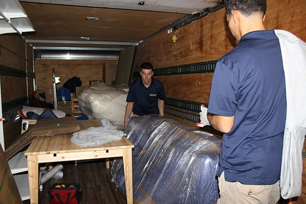 Guys from Suburban Solutions' junk hauling team loading an unwanted couch in one of our truck trailers