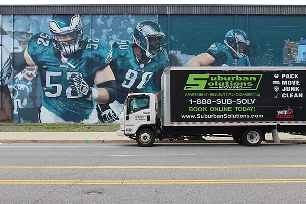 Suburban Solutions' moving truck parked in a side street in front of Philadelphia Eagles wall mural