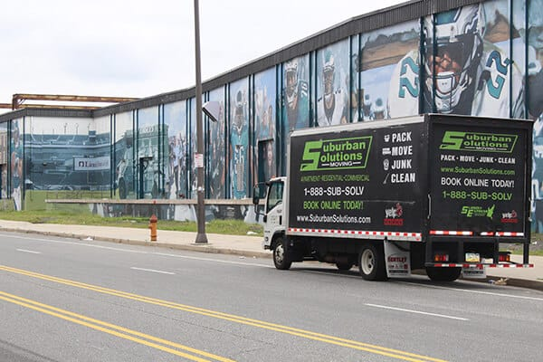 Suburban Solutions' moving truck parked beside Philadephia Eagles wall mural