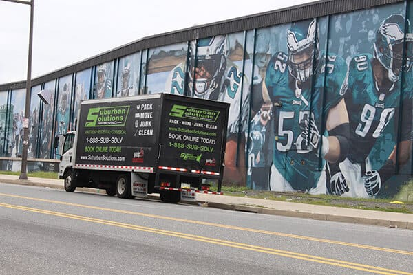 Suburban Solutions' moving truck caught in front of the wall mural with Philadelphia Eagles